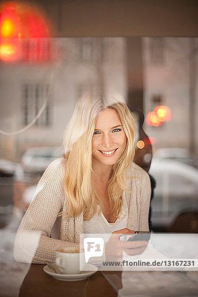 Porträt einer jungen Frau mit Handy in der Hand im Cafe