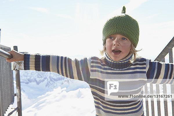 Junge in verschneiter Landschaft  der sich am Geländer festhält