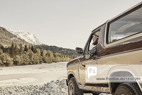 Mittelgroßer erwachsener Mann im Pickup  lehnt aus dem Fenster und schaut auf ein Gebirge  Wallgau  Bayern  Deutschland