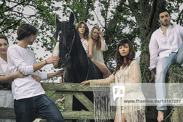 Portrait of six young adults and horse at forest gate