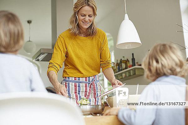 Frau serviert Mahlzeit am Esstisch