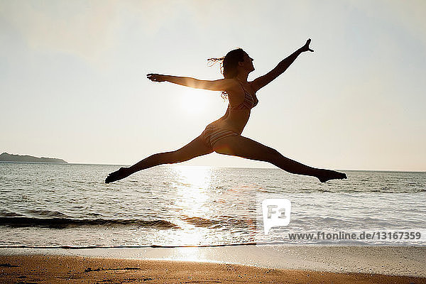 Frau springt am Strand über Wellen