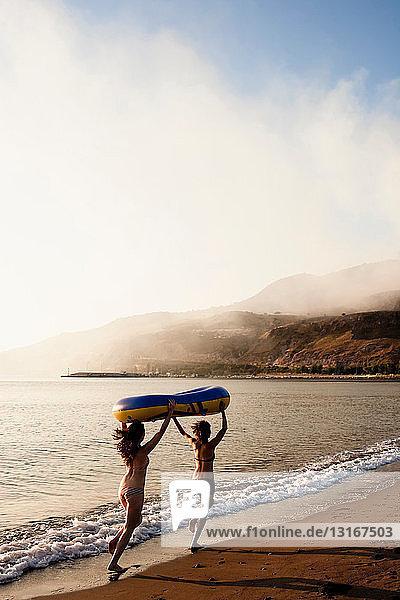 Frauen tragen Schlauchboot am Strand