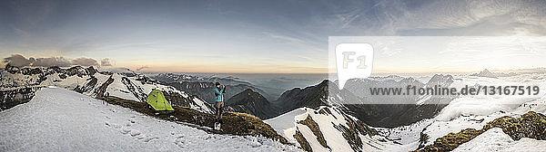 Panorama eines jungen männlichen Bergwanderers  der mit einem Smartphone in den bayerischen Alpen fotografiert  Oberstdorf  Bayern  Deutschland
