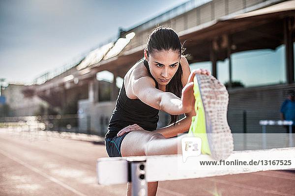 Junge Frau streckt Bein auf Hürde