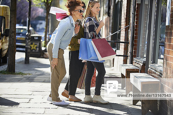 Side view of women holding shopping bags standing in street looking in shop window