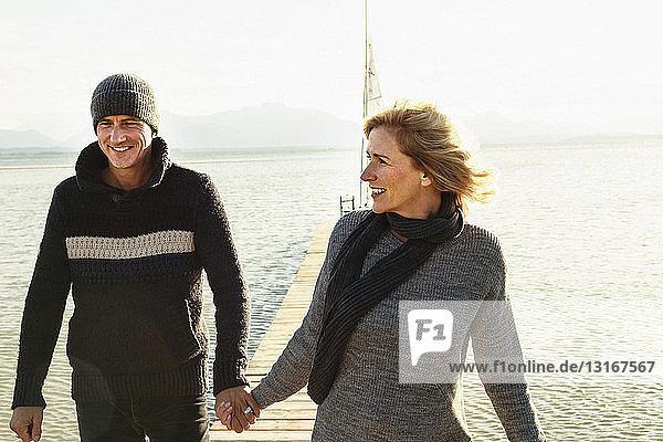 Reifes Paar auf dem Steg  Händchen haltend  lächelnd