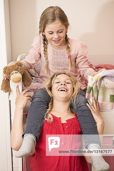 Girl laughing whilst giving sister a shoulder ride in bedroom