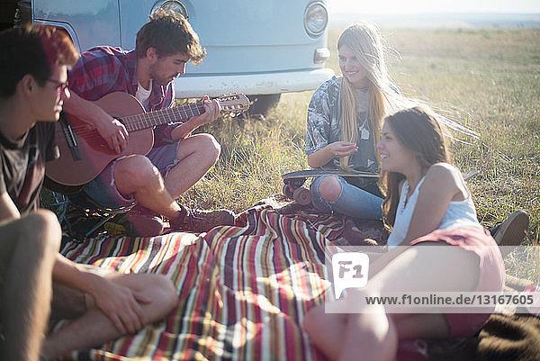 Freunde auf Picknickdecke mit Gitarre spielendem Mann