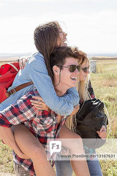 Drei Freunde beim Wandern  Mann gibt Frau Huckepack