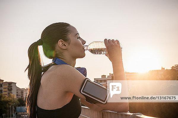 Junge Frau trägt Armbinde Trinkwasser
