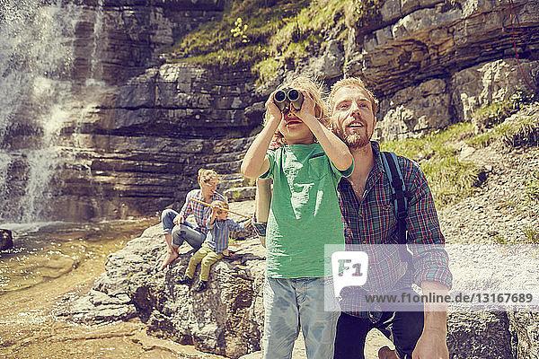 Junge Familie auf Erkundungstour am Wasserfall