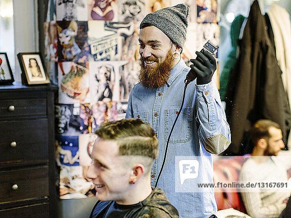 Friseur rasiert Haare junger Männer mit Haarschneidemaschine