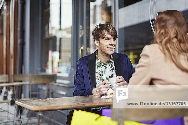Over shoulder view of couple chatting at sidewalk cafe  London  UK