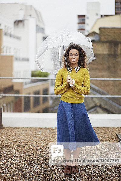 Weibliche Büroangestellte auf dem Dach  die einen Regenschirm hält
