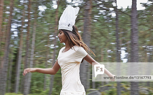 Teenage girl wearing white hat running in forest