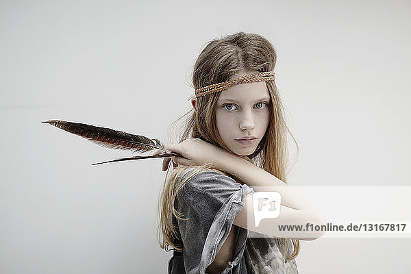 Portrait of girl wearing leather braid around head  holding feather