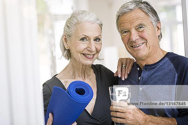 Älterer Mann und Frau halten Yogamatte und Wasserglas und schauen lächelnd in die Kamera