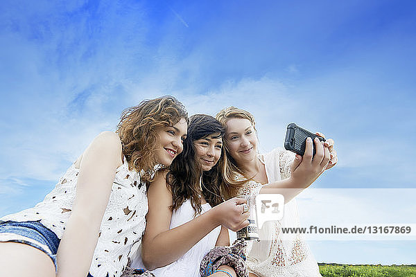 Three young women in field posing for selfie on smartphone