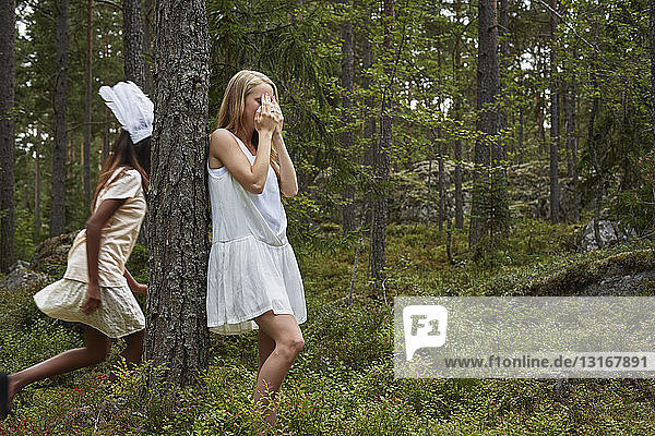 Teenage girls playing hide and seek in forest