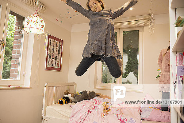 Girl jumping mid air from bed in bedroom
