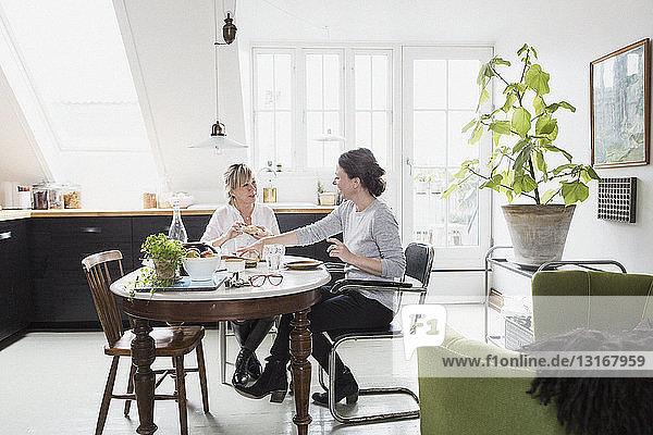 Zwei reife Frauen sitzen am Küchentisch und trinken Tee