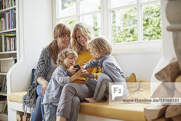 Erwachsene Frauen und Jungen sitzen auf einem Fensterplatz und schauen auf ein Smartphone