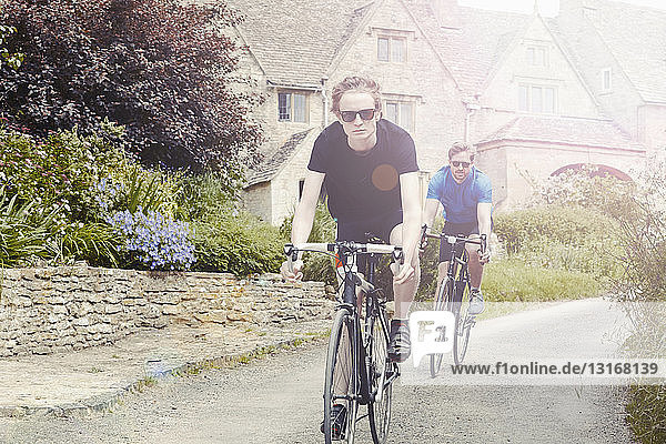 Cyclists riding through village  Cotswolds  UK