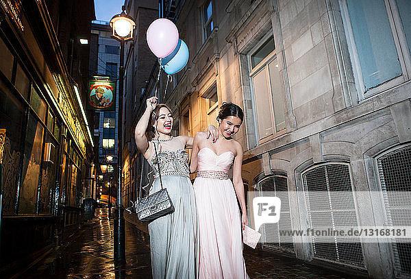 Zwei Freundinnen in Abendkleidern amüsieren sich in der Stadt