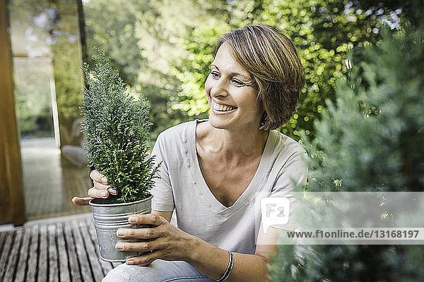 Reife Frau bereitet Topfpflanzen auf der Terrasse des neuen Hauses vor