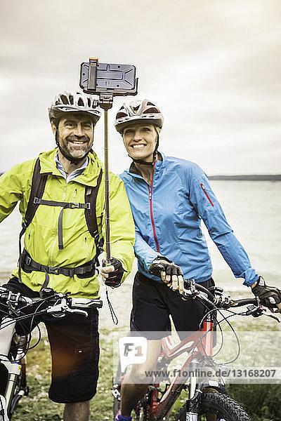 Älteres Mountainbike-Paar mit Smartphone-Selfie am Seeufer