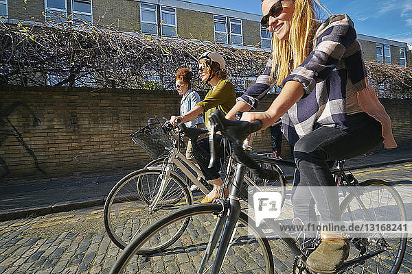 Side view of women cycling on bicycles on cobblestone road