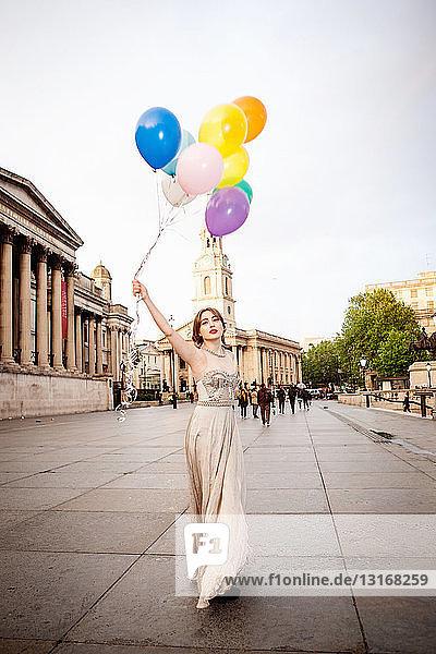 Junge Frau im Abendkleid  die Luftballons hochhält  Trafalgar Square  London  Großbritannien