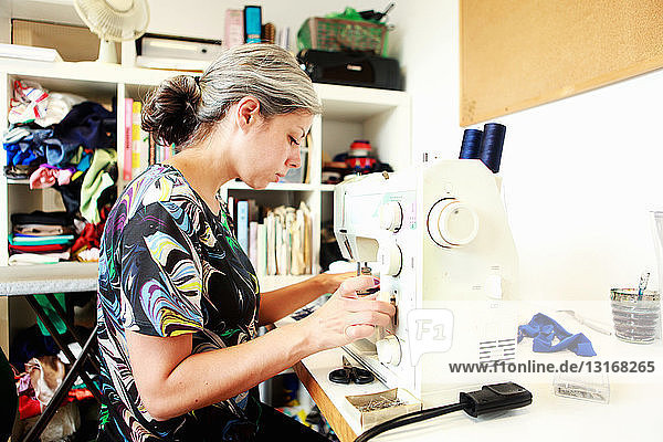 Designer working at sewing machine in studio