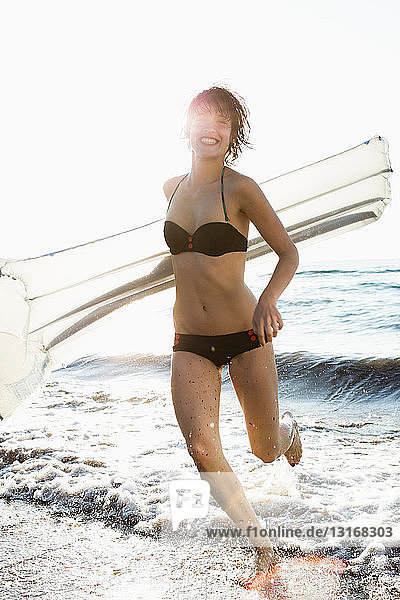Frau mit aufblasbarer Matratze am Strand