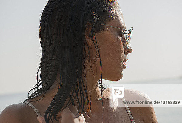 Portrait of beautiful young woman looking over her shoulder at coast