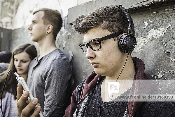 Teenager mit Kopfhörern  Freunde im Hintergrund