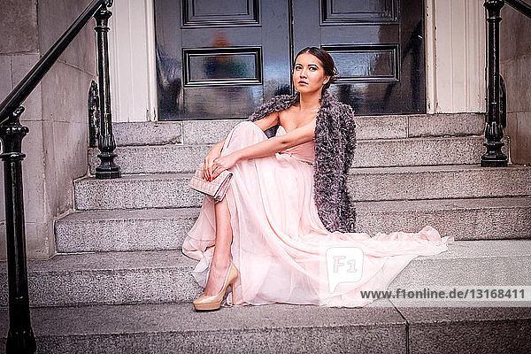 Porträt einer jungen Frau im Abendkleid  die auf einer Treppe sitzt