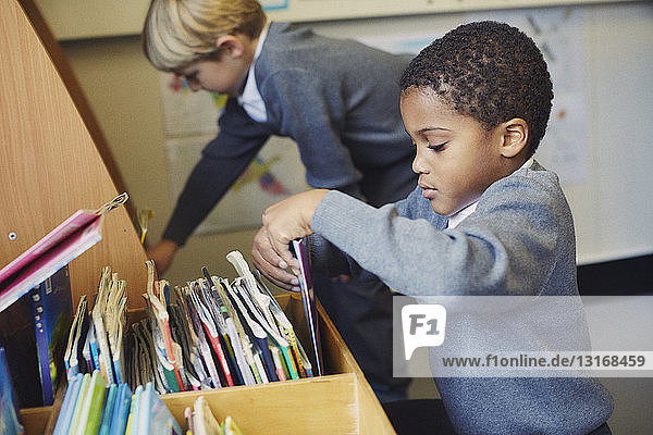 Two boys choosing books in elementary school classroom