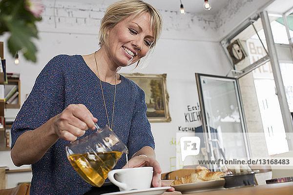 Mittlere erwachsene Frau  die im Café Tee einschenkt