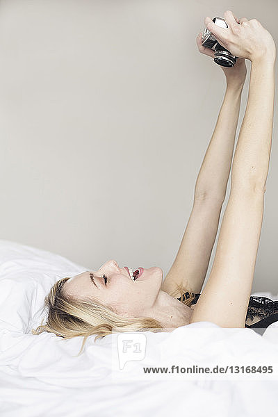 Junge Frau liegt auf dem Bett mit einer Kamera  die ein Selfie aufnimmt