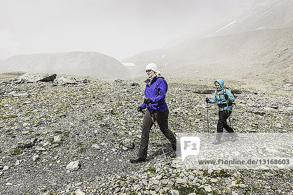 Two female hikers hiking in bleak landscape  Fil de Cassons  Segnesboden  Graubunden  Switzerland