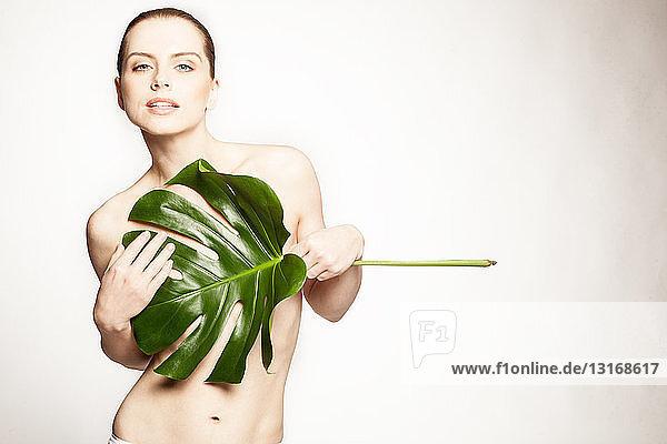Modell  das die Brüste mit großem Blatt bedeckt