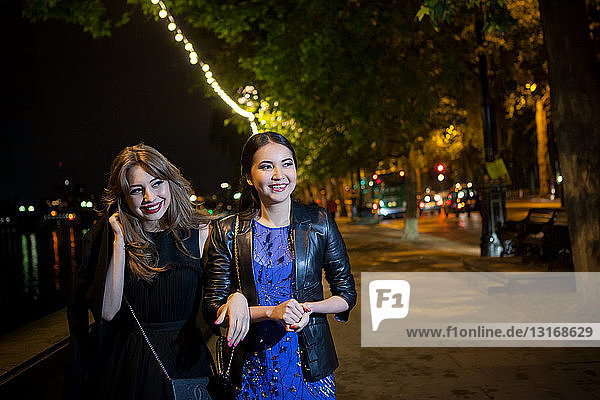 Zwei Freundinnen schlendern nachts am Flussufer entlang