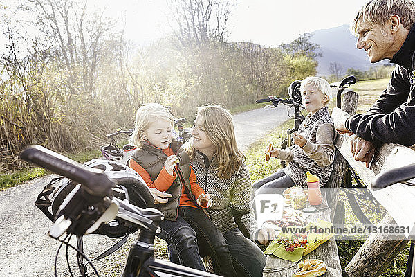Familie mit Fahrrädern  die sich auf einer Bank am Straßenrand ausruhen und lächelnd ein Picknick essen