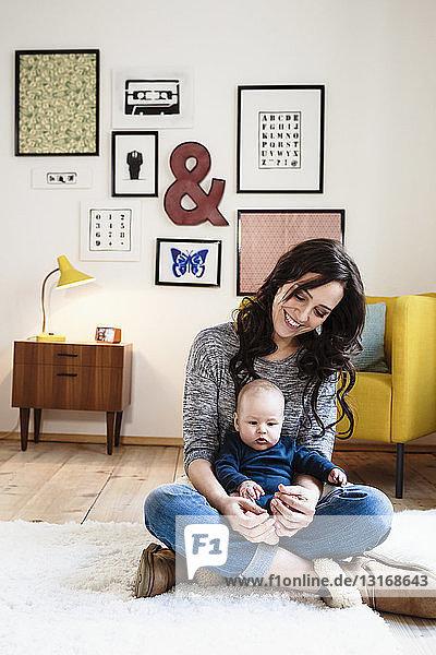 Mutter mit kleinem Sohn auf dem Schoß im Wohnzimmer