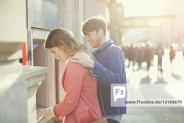 Couple withdrawing money from cash machine on street  London  UK