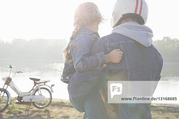Vater hält Tochter  am See  Vater mit Sturzhelm  Rückansicht