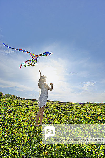 Young woman flying a kite in field