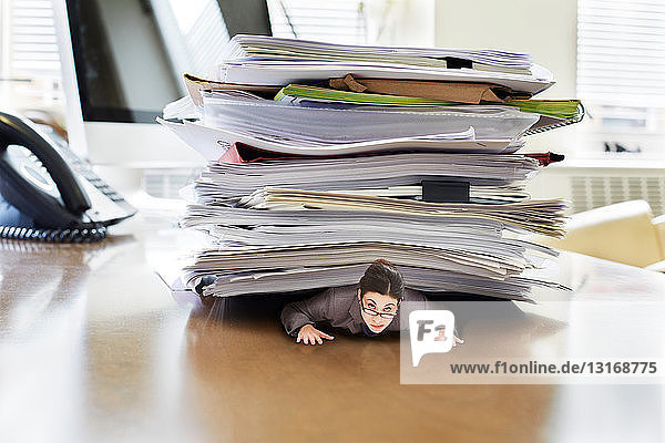Businesswoman trapped underneath stack of large documents on oversized desk  portrait